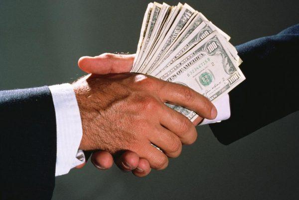 Один мужчина передаёт другому деньги