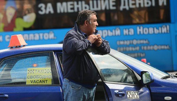 Водитель такси задумчиво стоит у автомобиля