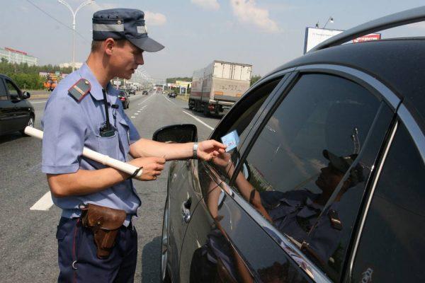 Инспектор ГИБДД рядом с тонированным автомобилем