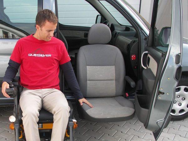 Мужчина на инвалидном кресле рядом с машиной