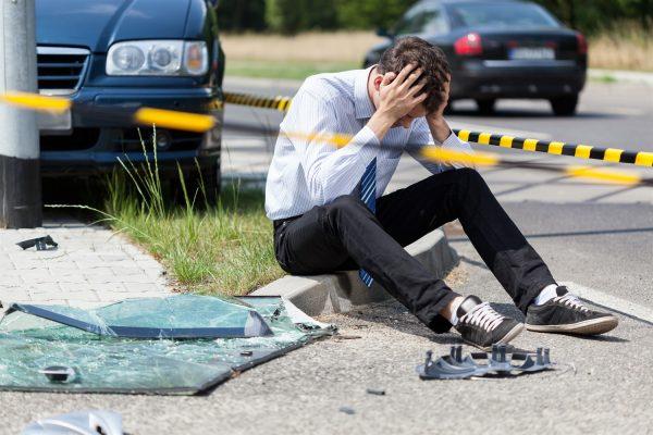 Мужчина сидит на земле после ДТП