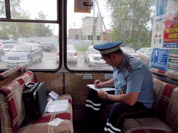 Инспектор ГИБДД оформляет документ в автобусе