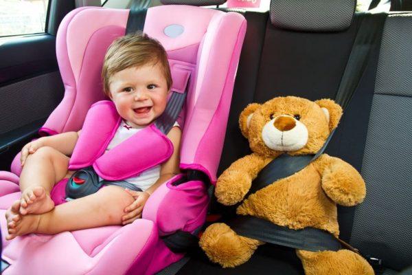 Ребёнок сидит в детском автокресле в машине, пристёгнутый ремнями безопасности