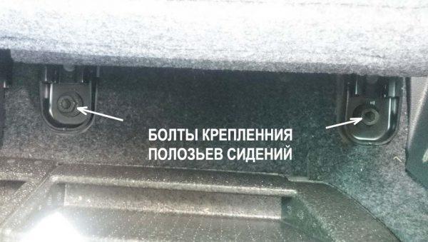 Болты, крепящие задние сидения со стороны багажника